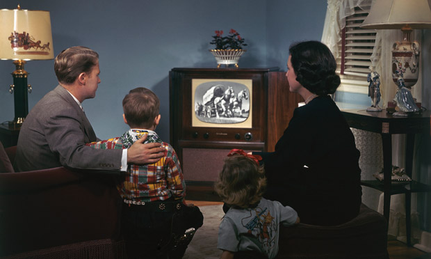 A young 1950s family watching television